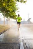 Młody brunetka mężczyzna robi ranku jog outdoors na jego smartphone podczas gdy słuchający muzyka w hełmofonach Zdjęcia Stock