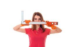 Młody brunetki kobiety budowniczy patrzeje i pozuje w mundurze robi odświeżaniom z narzędziami w jej rękach na kamerze odizolowyw Zdjęcia Stock