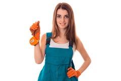 Młody brunetki kobiety budowniczy w mundurze i rękawiczkach robi odświeżaniom i ono uśmiecha się na kamerze odizolowywającej na b Zdjęcie Royalty Free