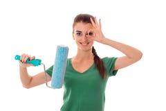 Młody brunetki kobiety budowniczy w mundurze robi odświeżaniom z farba rolownikiem w ona rękom przyglądające i ono uśmiecha się n Fotografia Stock