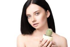 Młody brunetki kobiety mienia kaktus w garnku i patrzeć kamerę Fotografia Stock