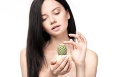 Młody brunetki kobiety mienia kaktus w garnku i wzruszających cierniach Obraz Royalty Free