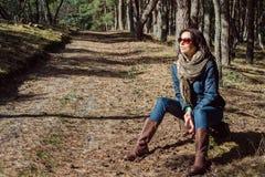 Młody brunetki kobiety obsiadanie na fiszorku w drewnach fotografia royalty free