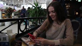 Młody brunetki kobiety obsiadanie w kawiarni używać jej telefon komórkowego, texting i pisać na maszynie, zbiory