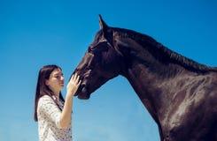 Młody brunetki piękno ma zabawę z koniem Słoneczny dzień, niebieskie niebo jako tło Piękna kobieta i czarny ogier Fotografia Stock