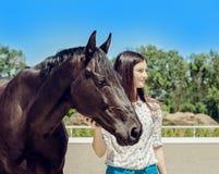 Młody brunetki piękno ma zabawę z koniem Słoneczny dzień, niebieskie niebo jako tło Piękna kobieta i czarny ogier Zdjęcie Royalty Free