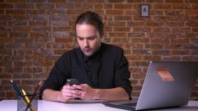 Młody caucasian biznesmen patrzeje telefon beznadziejnie i myśleć przy jego pracującym miejscem blisko ściana z cegieł