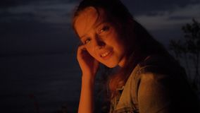 Młody caucasian dziewczyny obsiadanie ogieniem w naturze i patrzeć dzikiego ogienia, portret zbiory