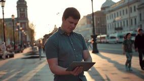 Młody caucasian mężczyzna żegluje w mieście używa pastylka komputeru osobistego komputer zdjęcie wideo
