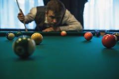 Młody caucasian mężczyzna bawić się billiards przygotowywających strzelać obrazy stock
