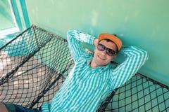 Młody caucasian mężczyzna chlanie w hamak przyjemnej gnuśności weekendowy ranek Zdjęcia Stock