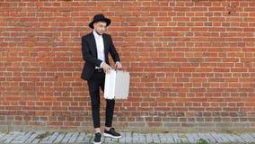 Młody caucasian mężczyzna w czarnym kostiumu i otwiera metal walizkę z pieniądze na ściany z cegieł tle, zwolnione tempo zdjęcie wideo