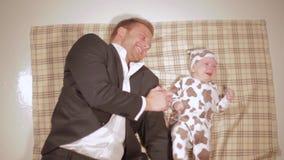 Młody caucasian mężczyzna w kostiumu kłama na brown sztukach z krzyczącym dzieckiem i koc zbiory wideo