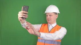 Młody caucasian mężczyzna w sygnałowej kamizelce i budowa hełmie bierze selfie na telefonie przy budową zbiory