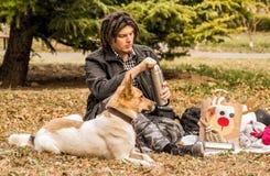 Młody caucasian mężczyzna z afro fryzurą na pinkinie z jego psem Zdjęcia Stock