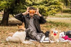 Młody caucasian mężczyzna z afro fryzurą na pinkinie z jego psem bawić się z pomarańczami Zdjęcie Stock