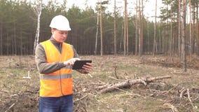 Młody caucasian męski forester w sygnałowej kamizelce i hełmie nagrywa dane na lesie caroyed przeciw zbiory