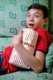 Młody caucasian nastoletni chłopak ogląda strasznego film fotografia stock