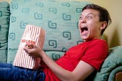 Młody caucasian nastoletni chłopak ogląda strasznego film zdjęcia royalty free