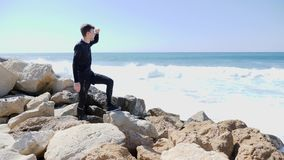 Młody caucasian uśmiechnięty mężczyzna patrzeje ocean z rękami przewodzić i wskazuje palec horyzont podczas gdy stojący na r zdjęcie wideo