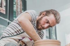 Młody ceramiczny artysta pracuje na jego glinianym garnku w studiu zdjęcie stock