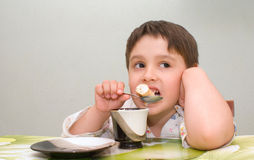 Młody chłopiec łasowania jedzenie przy stołem Fotografia Stock