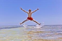 Młody chłopiec doskakiwanie z wody Fotografia Royalty Free