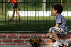 Młody chłopiec dziecka dopatrywania mecz futbolowy dla siatki Obrazy Royalty Free