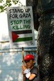Młody chłopiec mienia plakat przy Gaza: Zatrzymuje masakra wiec w Whitehall, Londyn, UK fotografia stock