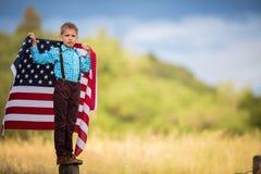 Młody chłopiec mienie z flaga amerykańską pokazuje patriotyzm dla jego swój kraju, Jednoczy stany Zdjęcia Royalty Free