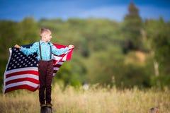 Młody chłopiec mienie z flaga amerykańską pokazuje patriotyzm dla jego swój kraju, Jednoczy stany zdjęcie royalty free
