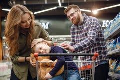 Młody chłopiec obsiadanie w zakupy tramwaju w supermarkecie Zdjęcie Stock