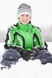 Młody chłopiec obsiadanie w zima śniegu Zdjęcie Royalty Free