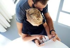 Młody chłopiec obsiadanie z ojcem i macanie ekranem komputer osobisty pastylka w pogodnym nowożytnym loft Horyzontalny, zamazany  Zdjęcia Stock