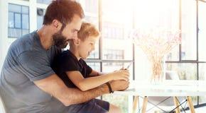 Młody chłopiec obsiadanie z ojcem przy stołem i bawić się wpólnie komputer osobisty pastylkę w nowożytnym loft Horyzontalny, zama Zdjęcia Stock