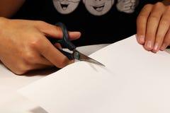 Młody chłopiec rozcięcia papier z nożycami przy szkołą dla niektóre egzaminu zdjęcie stock