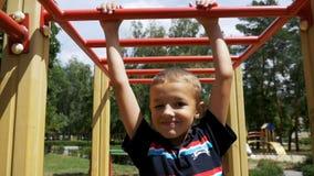 Młody chłopiec zrozumienie na Małpich barach jego rękami Ćwiczyć przy Plenerowym boiskiem przeciw niebu w zwolnionym tempie zdjęcie wideo