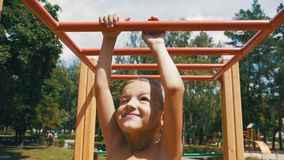 Młody chłopiec zrozumienie na Małpich barach jego rękami Ćwiczyć przy Plenerowym boiskiem przeciw niebu w zwolnionym tempie zbiory wideo
