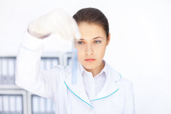 Młody chemiczny żeński badacz trzyma szklanej tubki z błękitnym fl Obrazy Royalty Free