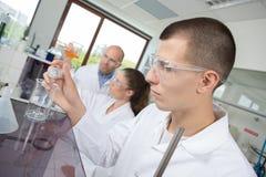 Młody chemik łączy chemicznego ciecz w lab zdjęcia royalty free