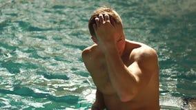 Młody chested mężczyzna pływa w basenie Facet bierze jego rękę kierowniczy i bawić się z włosy Jest przyglądający zdjęcie wideo