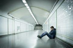 Młody chory mężczyzna gubił cierpienie depresji obsiadanie na zmielonym ulicznym metro tunelu Zdjęcia Stock