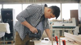 Młody cieśla używa wyrzynarki władzy instrument zobaczył drewno w warsztacie zbiory wideo