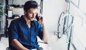 Młody coworker opowiada na jego telefonie komórkowym zamazujący tło horyzontalny Zdjęcie Stock