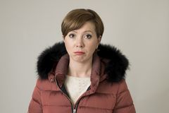 Młody cukierki i smutna czerwona włosiana kobieta pozuje patrzeć kamera jest ubranym ciepłą zima żakieta kurtkę z kapiszonem mark zdjęcie stock