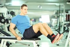 Młody człowiek ćwiczy brzusznego abs w sprawność fizyczna klubie na ławce Zdjęcia Stock