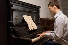 Młody człowiek ćwiczy przy pianinem Zdjęcia Royalty Free