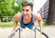Młody człowiek ćwiczy przy plenerowym gym Fotografia Royalty Free