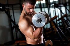 Młody człowiek ćwiczy z ciężarem w gym obraz royalty free
