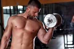 Młody człowiek ćwiczy z ciężarem w gym zdjęcia royalty free